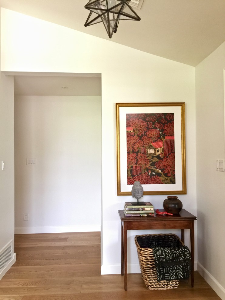 Entryway - mid-sized contemporary light wood floor entryway idea in Phoenix with white walls and a white front door