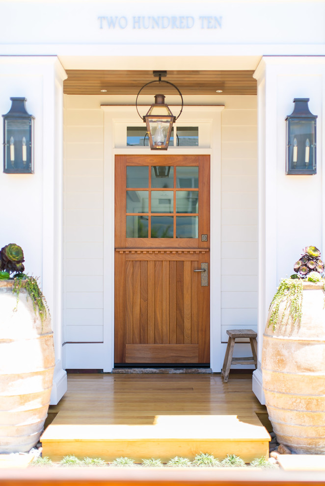 Inspiration for a mid-sized tropical medium tone wood floor and brown floor entryway remodel in Orange County with white walls and a medium wood front door