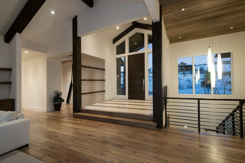 Example of a mid-sized trendy medium tone wood floor entryway design in Salt Lake City with white walls