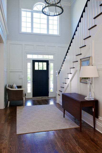 Example of a classic dark wood floor and brown floor entryway design in Other with a black front door and white walls