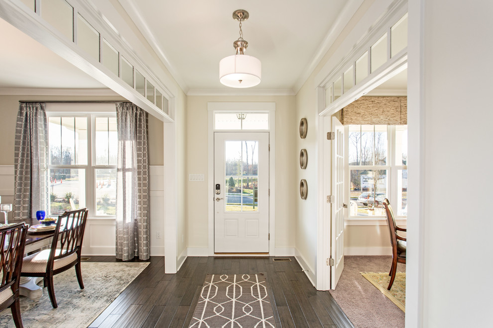 Example of a beach style dark wood floor entryway design in Richmond with beige walls and a white front door