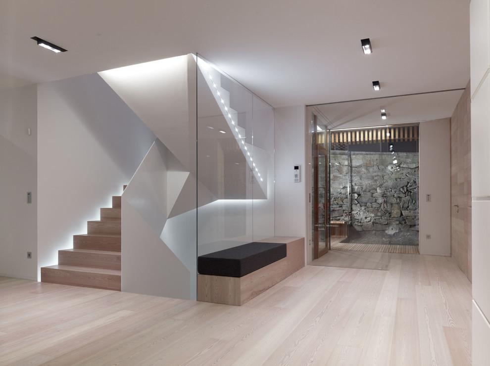 Immagine di un ampio ingresso design con pareti bianche, parquet chiaro e una porta in vetro