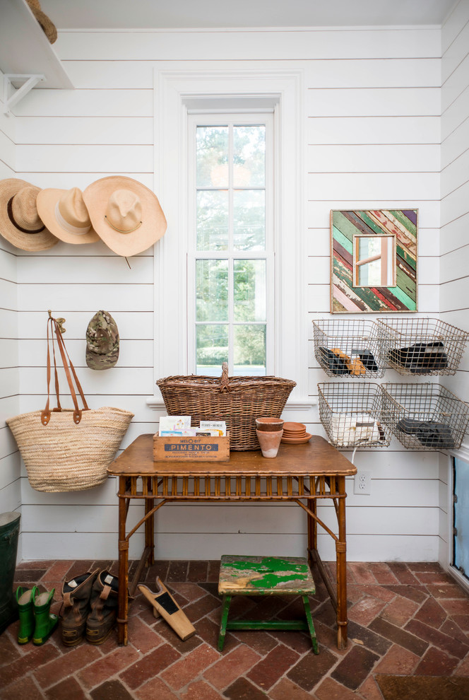 Country brick floor mudroom photo in Raleigh with white walls