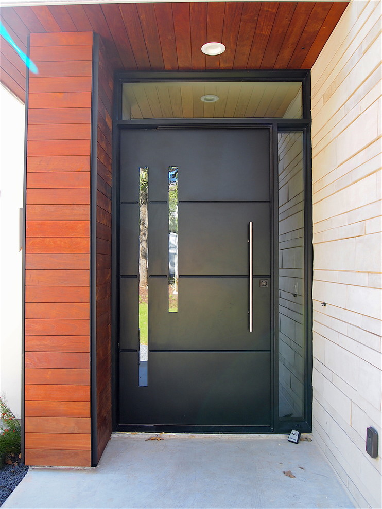 Mid-sized trendy concrete floor entryway photo in Austin with brown walls and a black front door