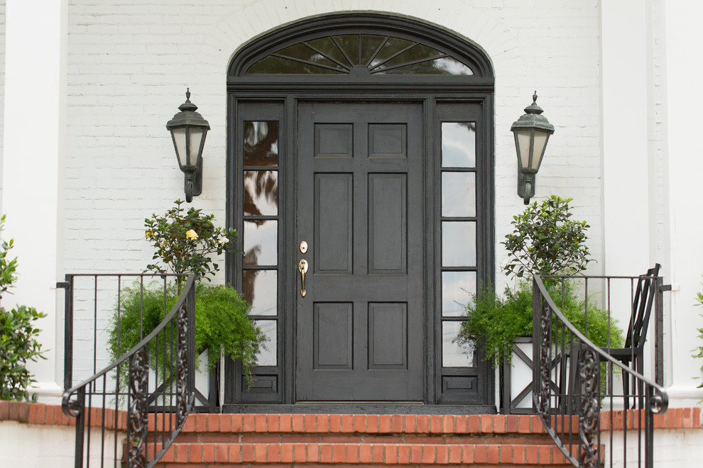 Example of a classic entryway design in Little Rock with a black front door
