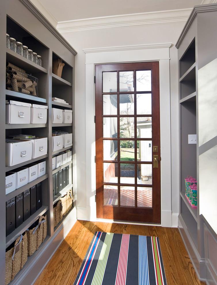 Elegant medium tone wood floor entryway photo in Atlanta with gray walls and a glass front door