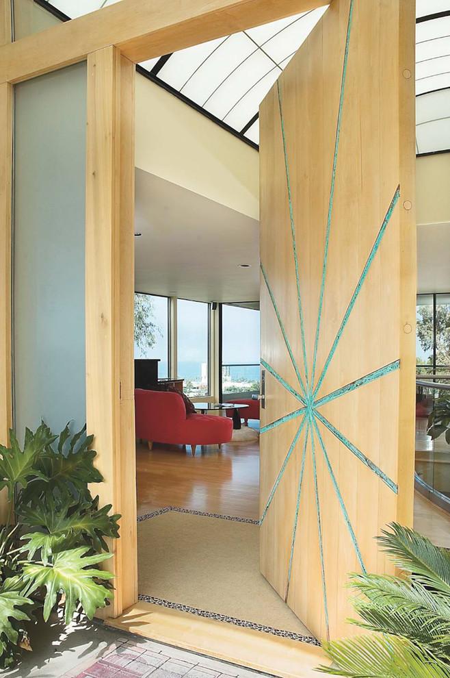 Trendy pivot front door photo in San Diego with a light wood front door