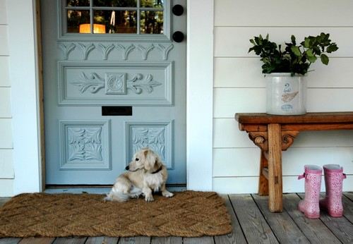 brown welcome rug by blue door