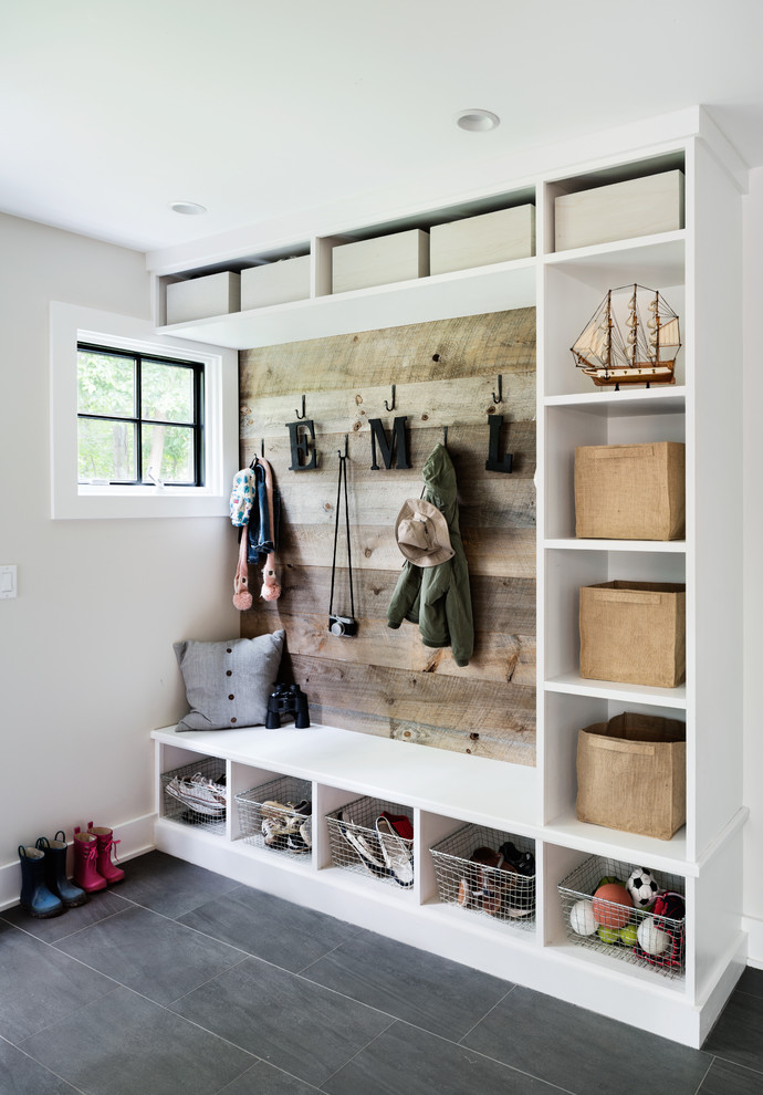 Beach style gray floor mudroom photo in New York with beige walls