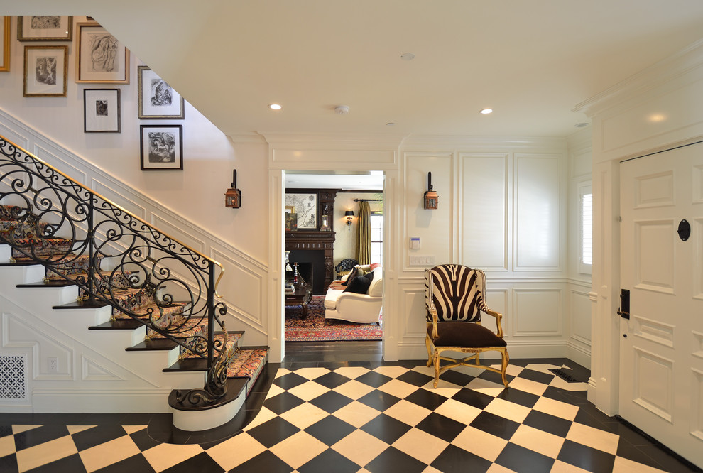 Elegant multicolored floor entryway photo in Los Angeles with white walls and a white front door