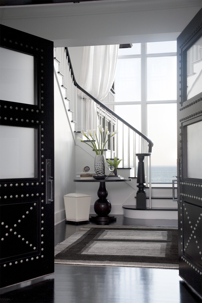 Example of a transitional dark wood floor and black floor foyer design in Boston with white walls