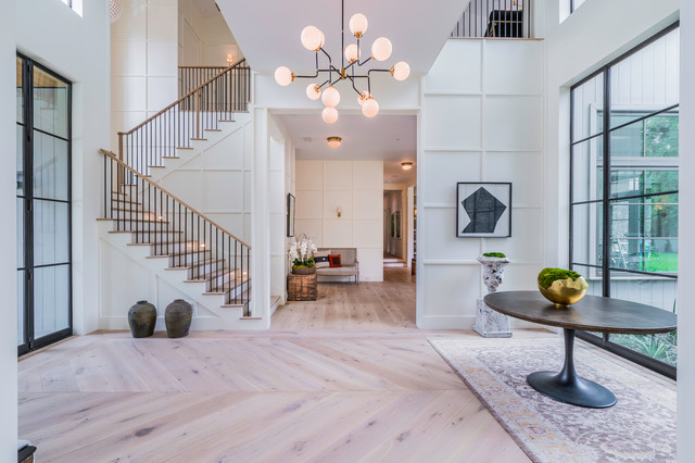 Example of a transitional light wood floor and beige floor entryway design in Los Angeles with white walls and a green front door