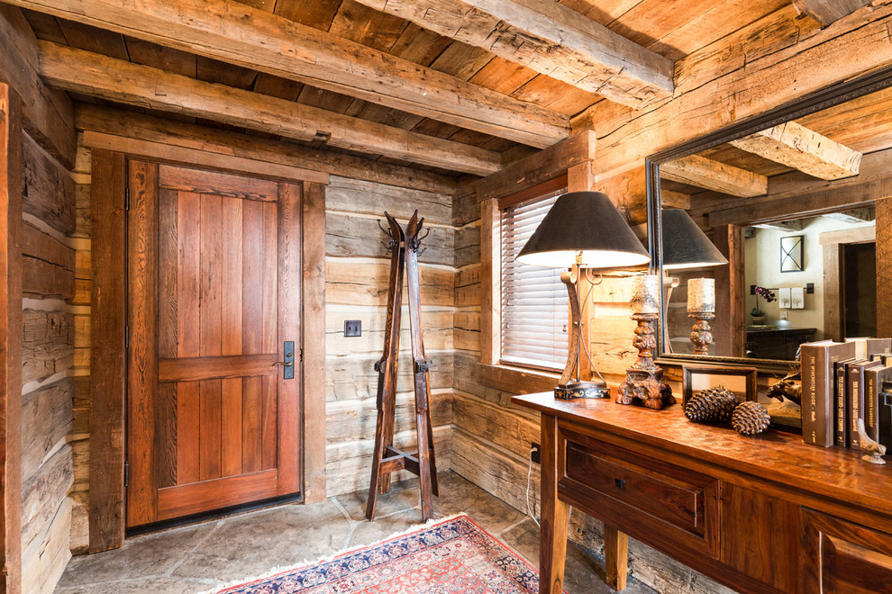 Inspiration for a rustic entryway remodel in Other with brown walls and a dark wood front door