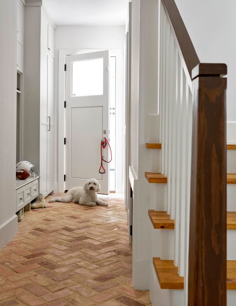Example of a farmhouse brick floor entryway design in Dallas with white walls and a white front door