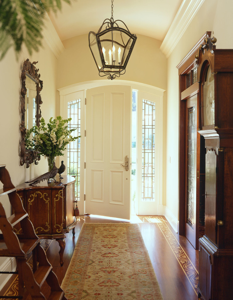 Entryway - traditional medium tone wood floor entryway idea in San Francisco with beige walls and a white front door