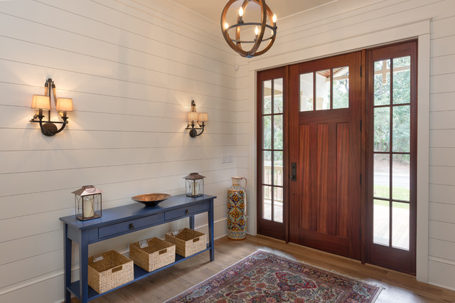 Example of a farmhouse light wood floor entryway design in Charleston with white walls and a dark wood front door