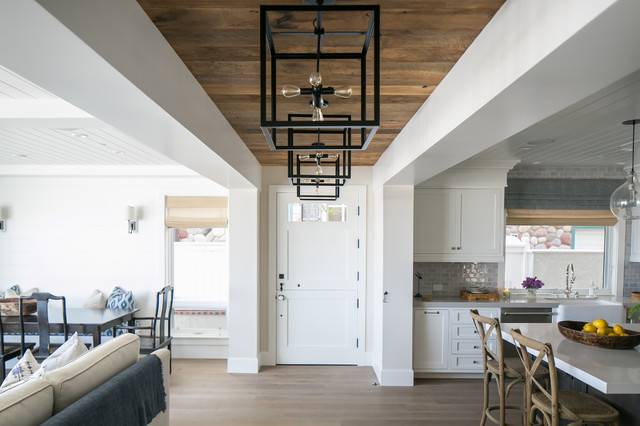 Coastal light wood floor entryway photo in Orange County with gray walls and a white front door