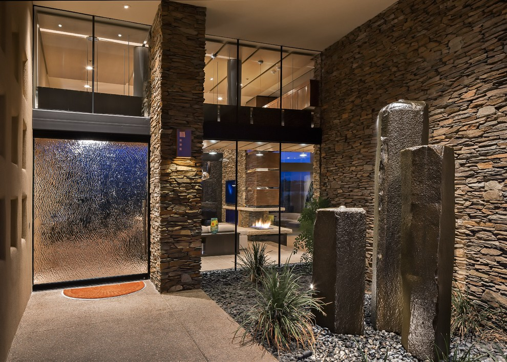 Entryway - large contemporary concrete floor entryway idea in Phoenix with beige walls and a glass front door