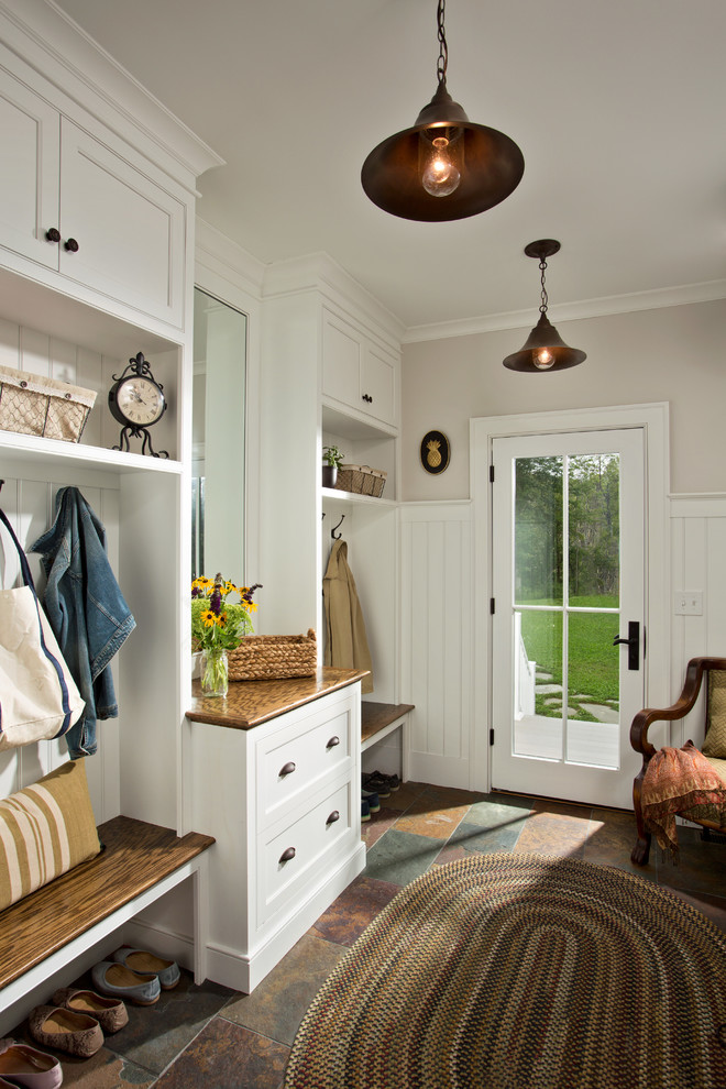 Example of a cottage entryway design in Boston with a glass front door and white walls