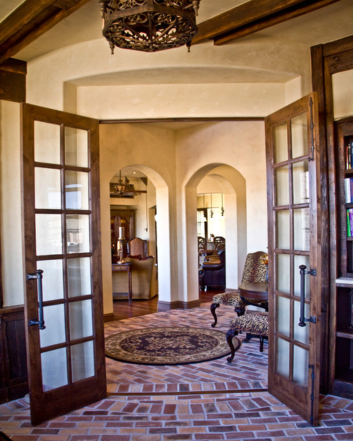 Example of a tuscan brick floor foyer design in Austin with beige walls