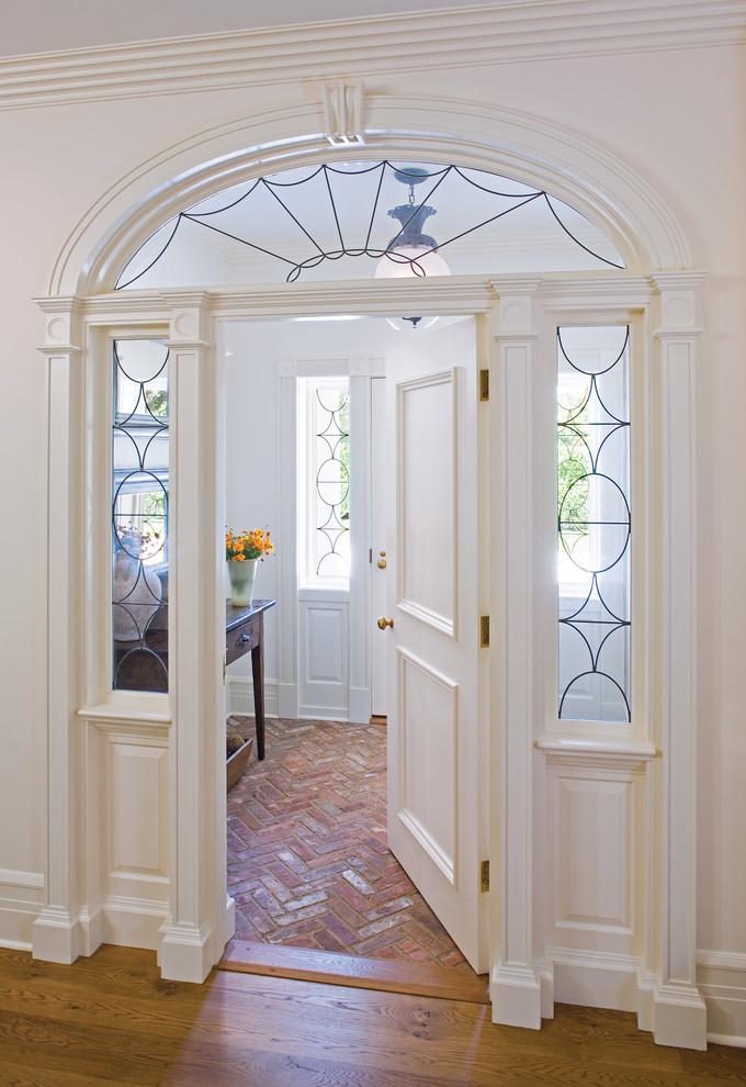 Elegant brick floor single front door photo in New York with white walls and a white front door