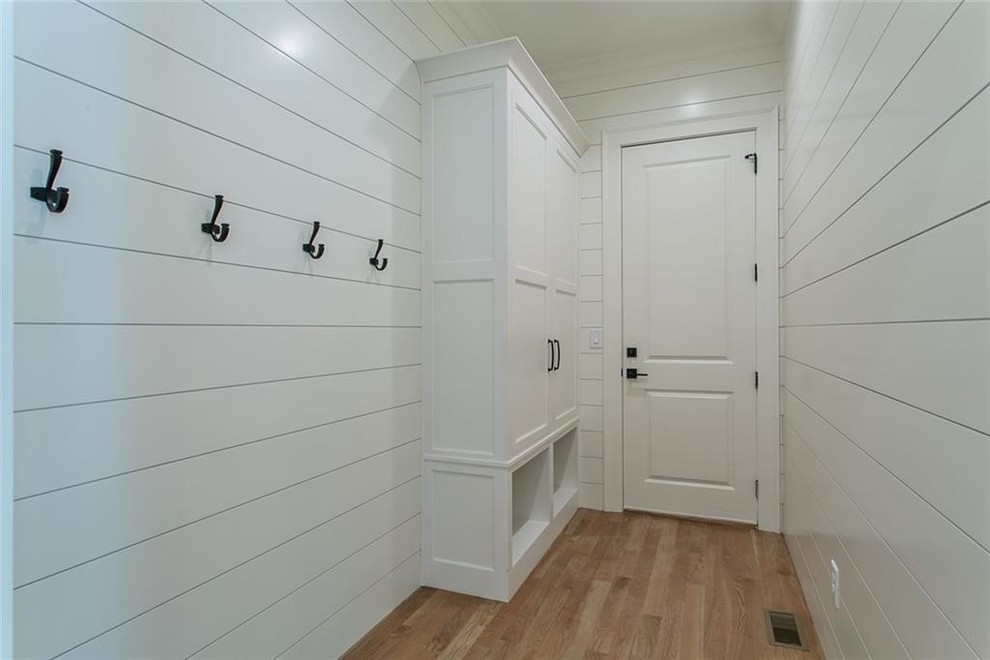 Inspiration for a mid-sized light wood floor and gray floor mudroom remodel in Atlanta with white walls