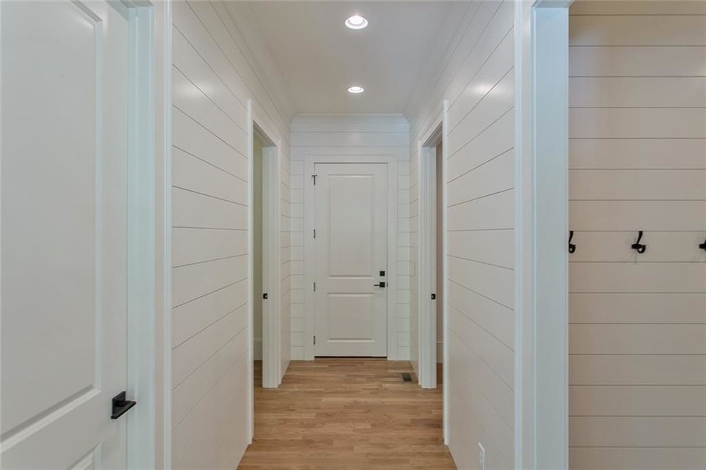 Example of a mid-sized light wood floor and gray floor mudroom design in Atlanta with white walls