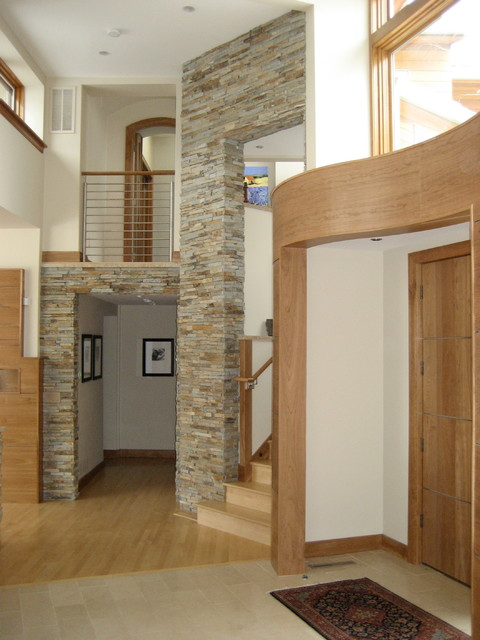 Example of a large trendy entryway design in Denver with a medium wood front door and beige walls