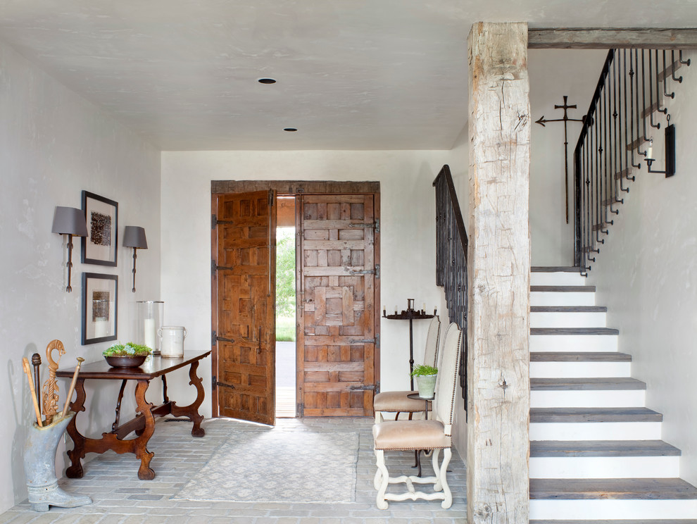 Example of a mountain style brick floor entryway design in Other with a medium wood front door and white walls