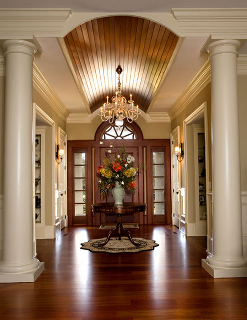 Stained arched ceiling enhances foyer and relates to front door. traditional entry