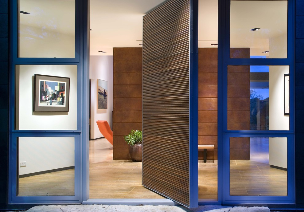 Modern entrance in Austin with a pivot front door and a medium wood front door.