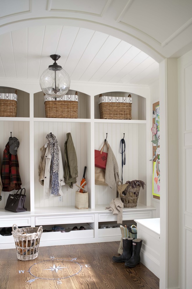Mudroom - traditional dark wood floor mudroom idea in New York with white walls