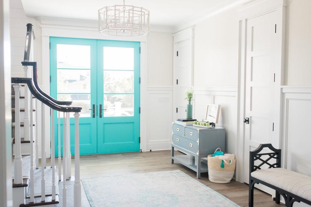 Modelo de entrada marinera con paredes blancas, suelo de madera en tonos medios, puerta doble, puerta azul y suelo marrón