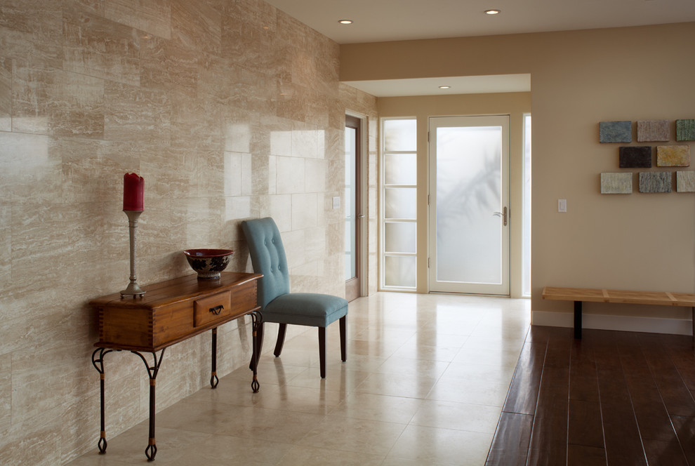 Example of a mid-sized trendy travertine floor entryway design in San Diego with beige walls and a glass front door