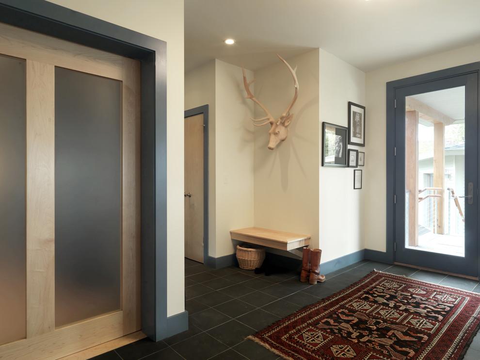 Single front door - contemporary black floor single front door idea in Burlington with beige walls and a glass front door