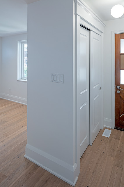 Example of a small transitional light wood floor and brown floor entryway design in Toronto with white walls and a brown front door