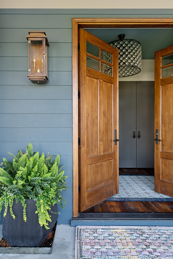 Entryway - mid-sized transitional entryway idea in Other with a medium wood front door and blue walls
