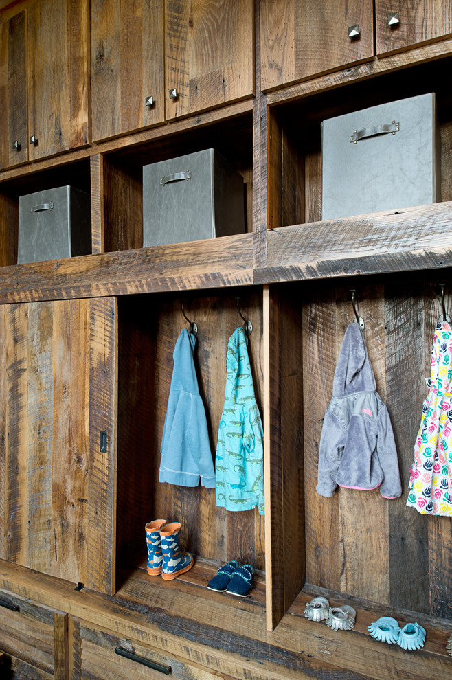 Inspiration for a mid-sized rustic mudroom remodel in Other with white walls