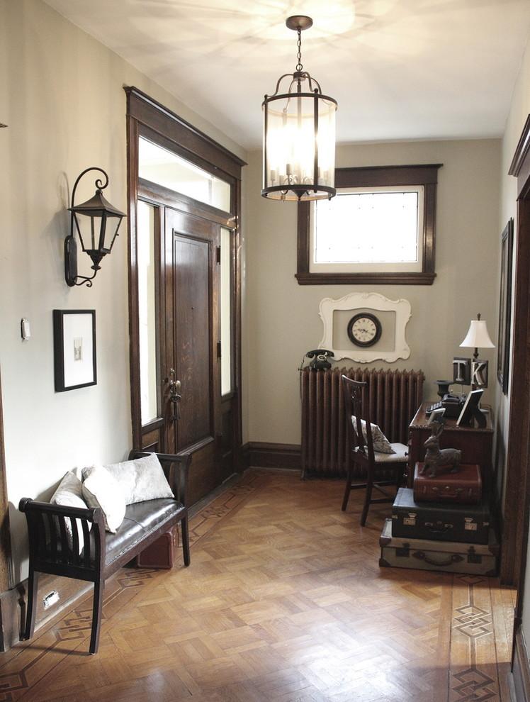 Eclectic medium tone wood floor single front door photo in Toronto with a dark wood front door