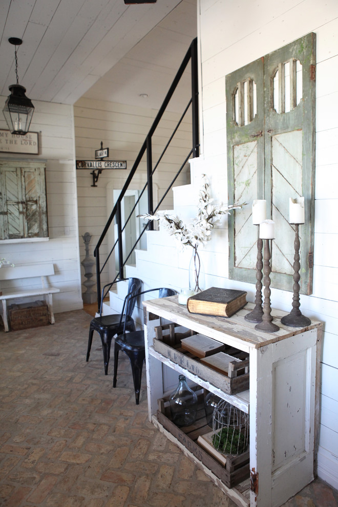 Inspiration for a mid-sized shabby-chic style brick floor entry hall remodel in Austin with white walls and a medium wood front door