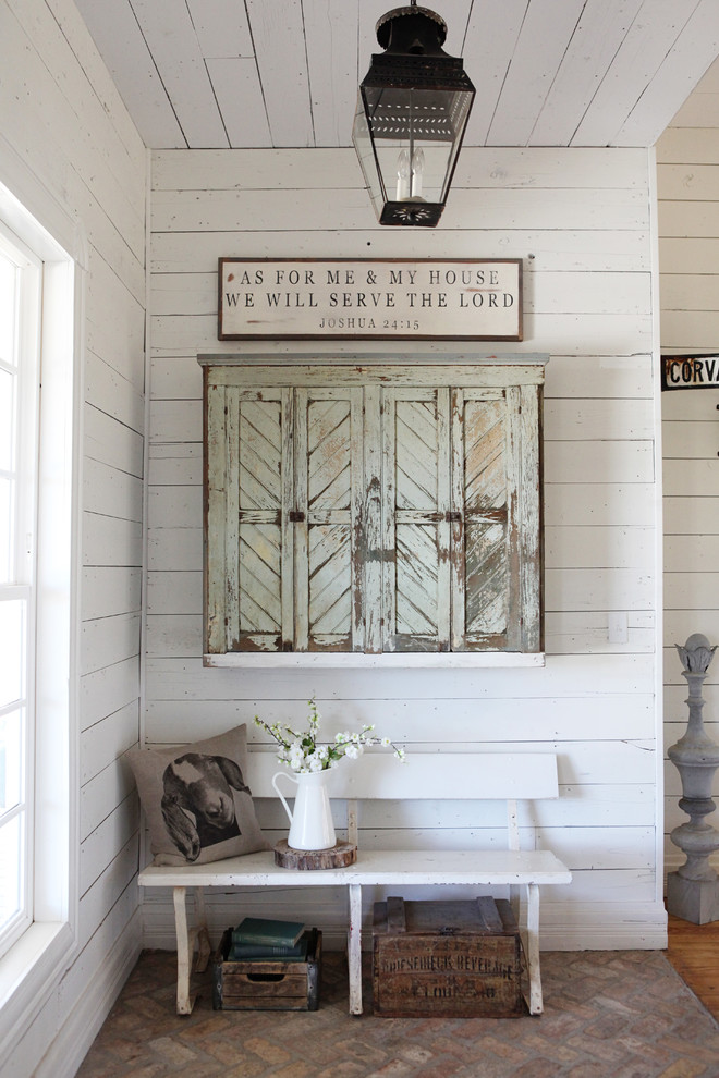 Entryway - mid-sized cottage brick floor entryway idea in Austin with white walls