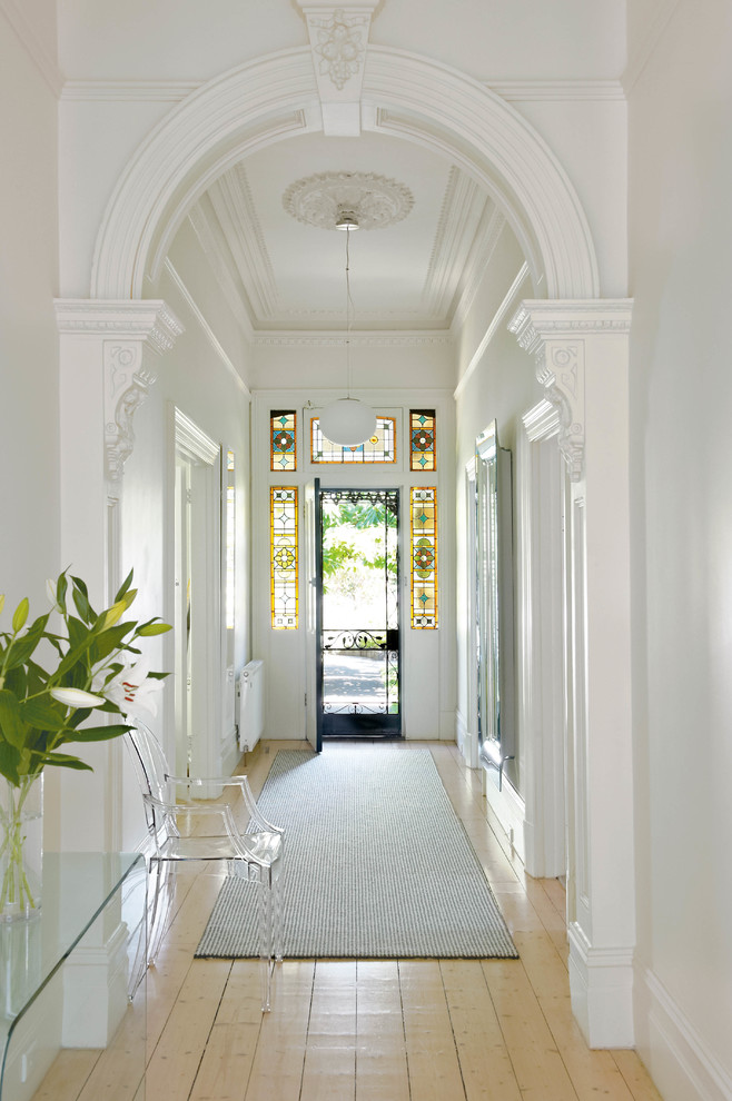 This is an example of a traditional entry hall in Melbourne with white walls, light hardwood floors, a single front door and a metal front door.