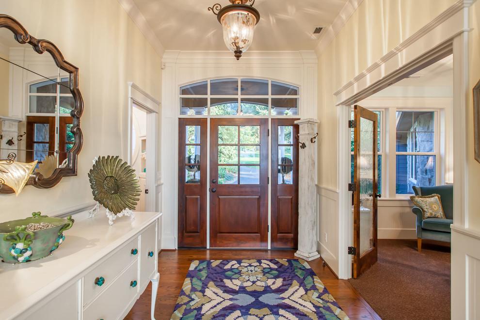 Imagen de puerta principal clásica, grande, con paredes amarillas, suelo de madera en tonos medios, puerta simple y puerta de madera en tonos medios