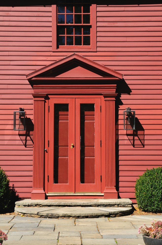 Inspiration for a mid-sized timeless slate floor entryway remodel in New York with red walls and a red front door