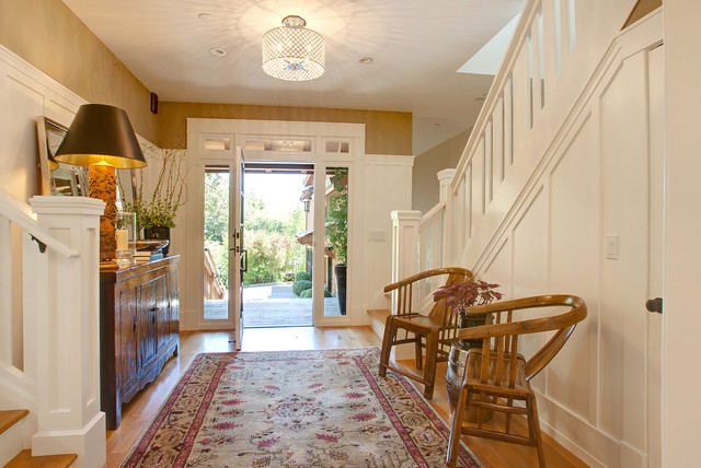 Example of a transitional medium tone wood floor entryway design in San Francisco with brown walls