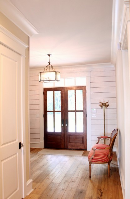 Example of a light wood floor entryway design in Other with white walls and a dark wood front door