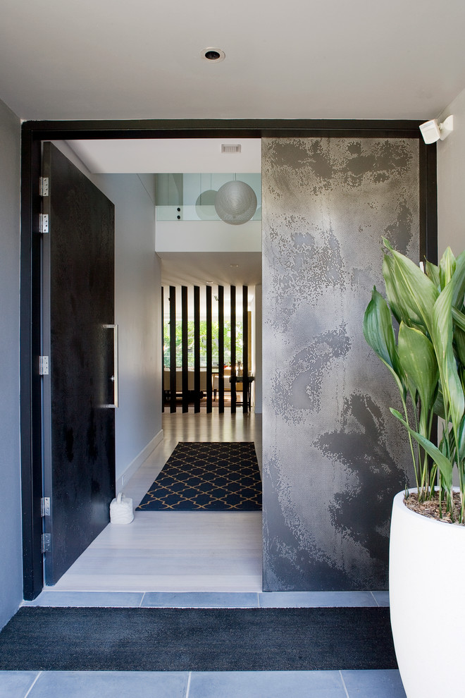 Inspiration for a contemporary entryway remodel in Sydney with white walls and a black front door