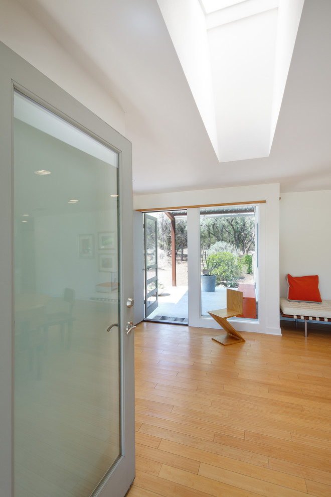 Minimalist light wood floor entryway photo in Austin with white walls and a glass front door