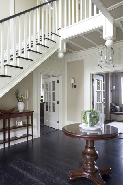 Example of a classic black floor entryway design in Dublin with beige walls