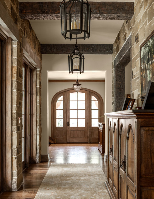 Tuscan entryway photo in Dallas with white walls